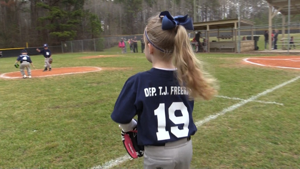 A member of the Crawford County Recreation Department Wee Ball Yankees wears fallen Bibb County Sheriff's Office Investigator T.J. Freeman's name across her back.