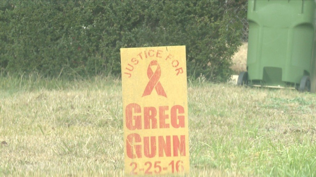 A sign sits in Greg Gunn's mothers front yard, just a few feet from where he was shot and killed.