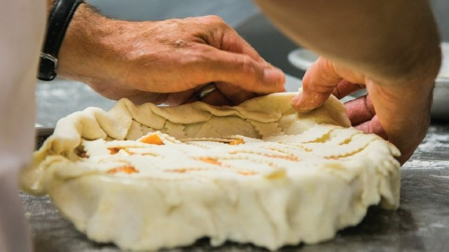 putting on the pie crust of a pie