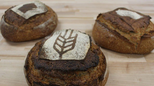 Three loaves of ORIGIN Breads with wheat and wisconsin symbol