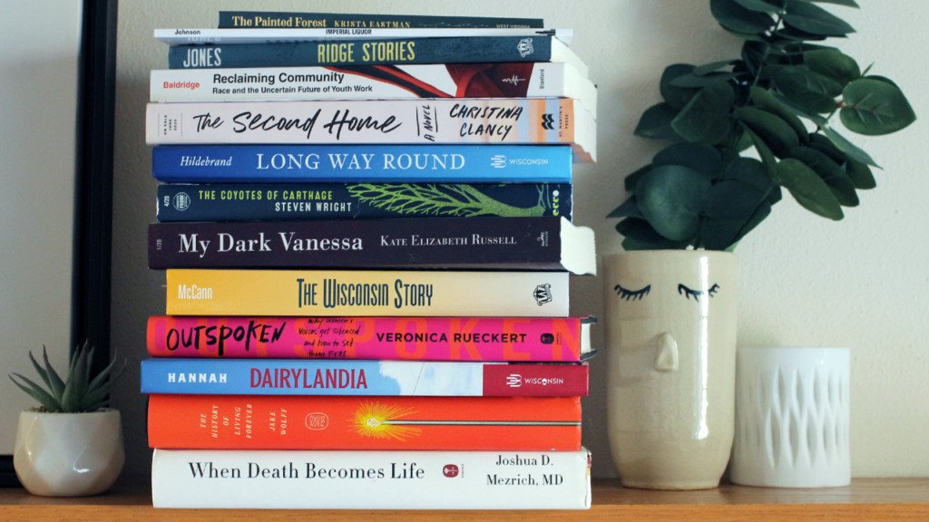 A stack of books on a mantle next to a vase, a candle holder and a succulent