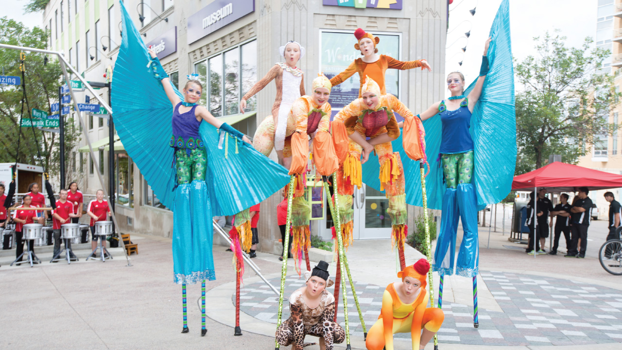 performers on stilts in front of the Madison Children's Museum
