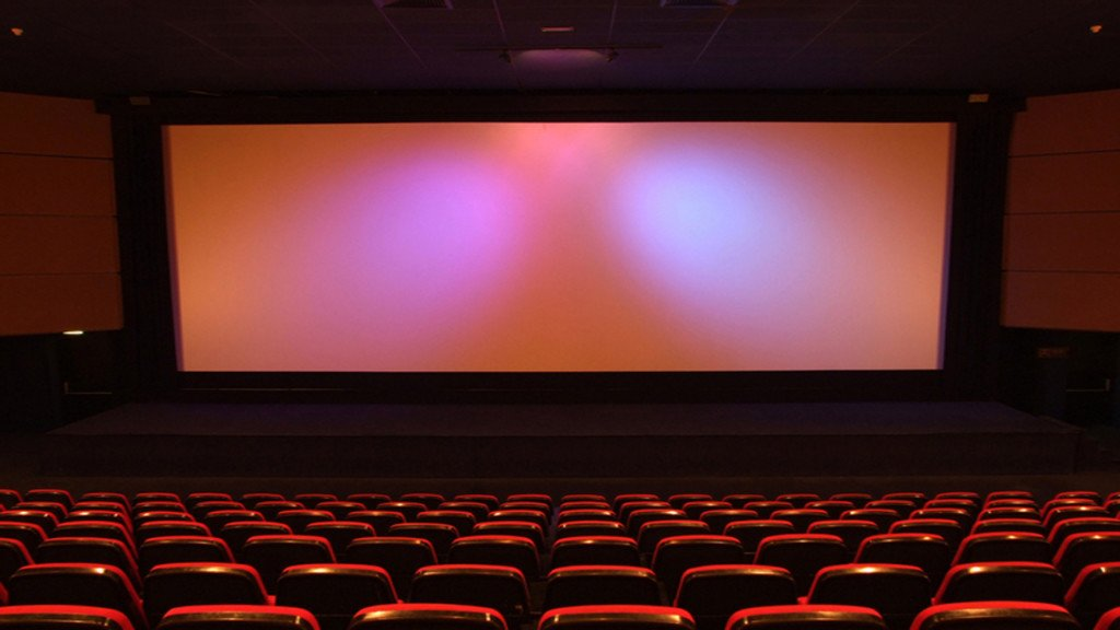 empty movie theater with red chairs and a big screen