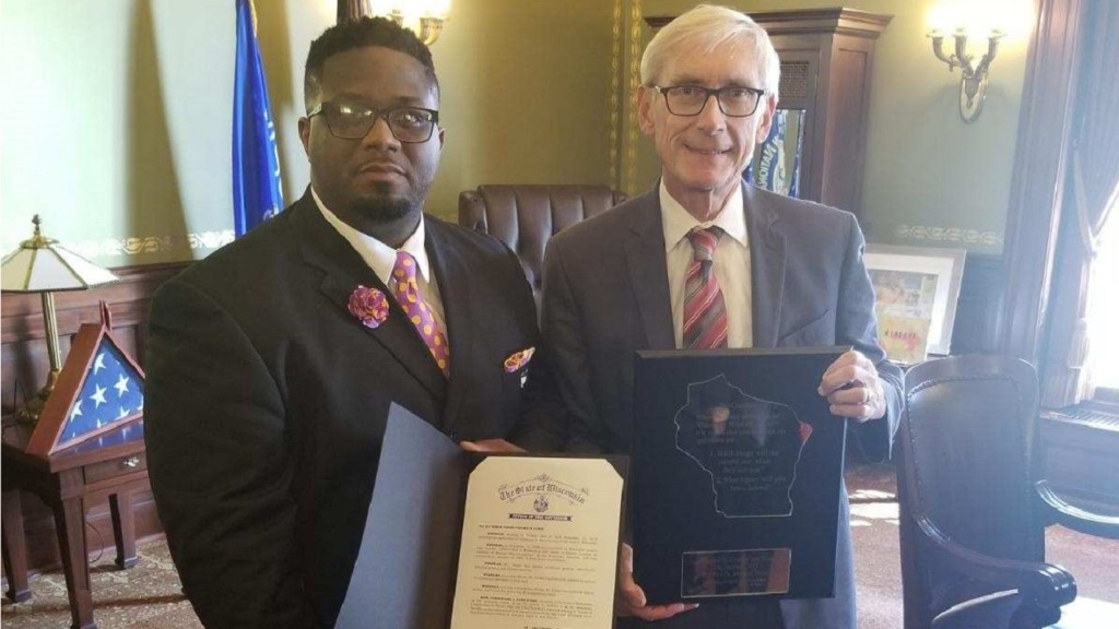'A new life beginning': Gov. Evers pardons associate minister, who presents him with plaque