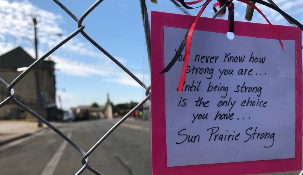 Fences surrounding Sun Prairie explosion site decorated with special notes, flowers