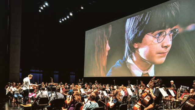 orchestra of musicians is in front of a screen with harry potter