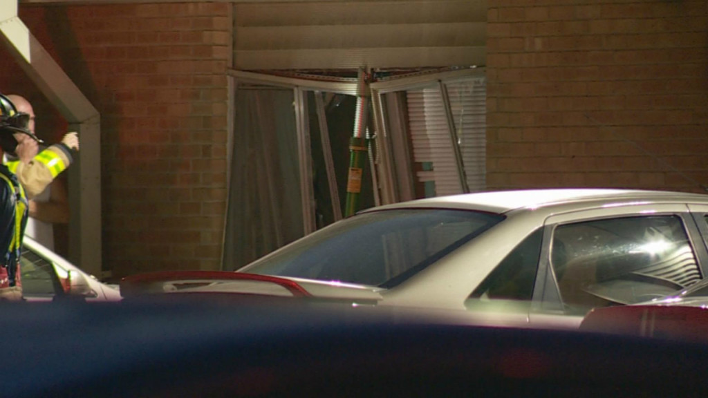 Car crashes into building, pushing brick siding, air conditioner into apartment, officials say