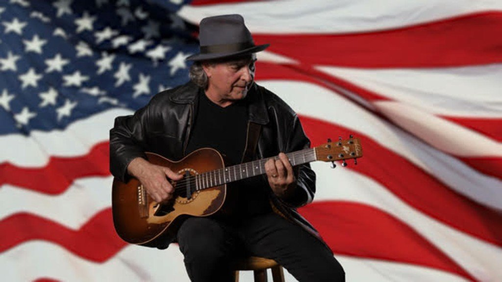 Musician Robert J. performs holding a guitar in front of an American flag as part of a patriotic protest
