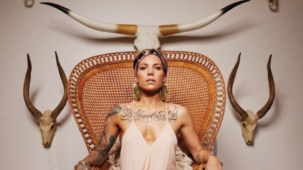 Skylar Grey sitting in a chair with horns around her