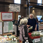 Two vendors: one selling meet and the other selling greens