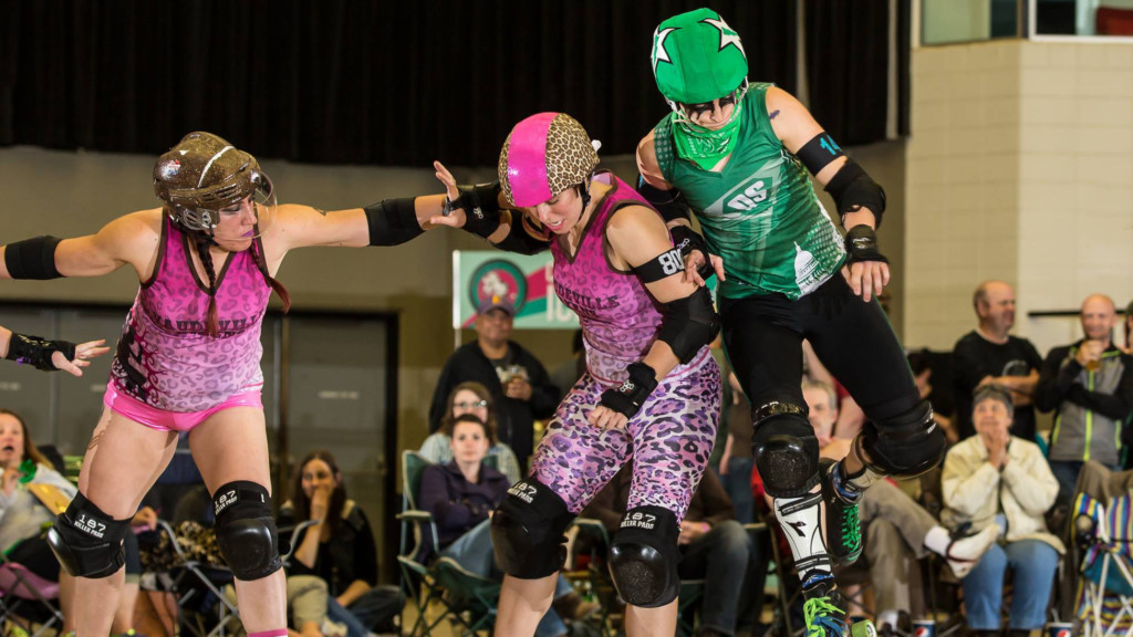 Three roller derby players on skates, one person is hitting another
