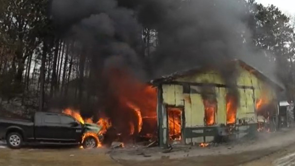 shed fully engulfed in flames with a truck nearby