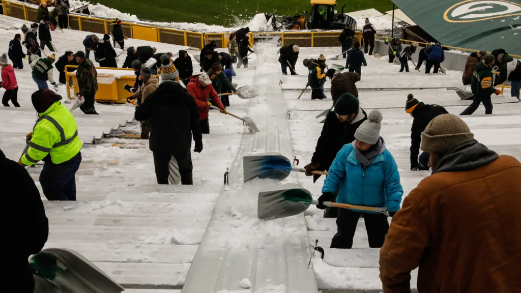 group of people in Lambeau Field with shovels for snow removal