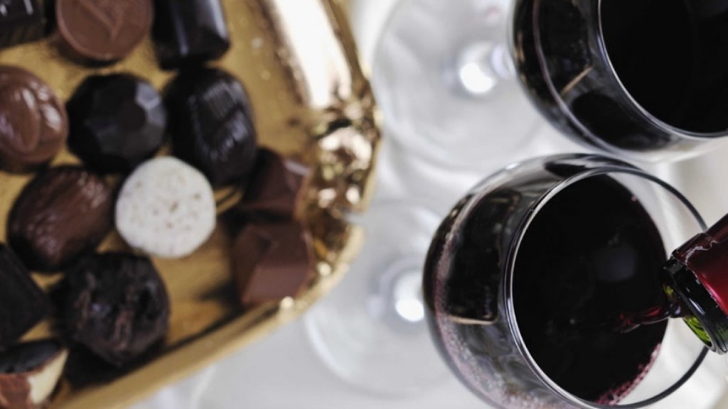 A plate of chocolates with two glasses of wine, one being poured into from a bottle