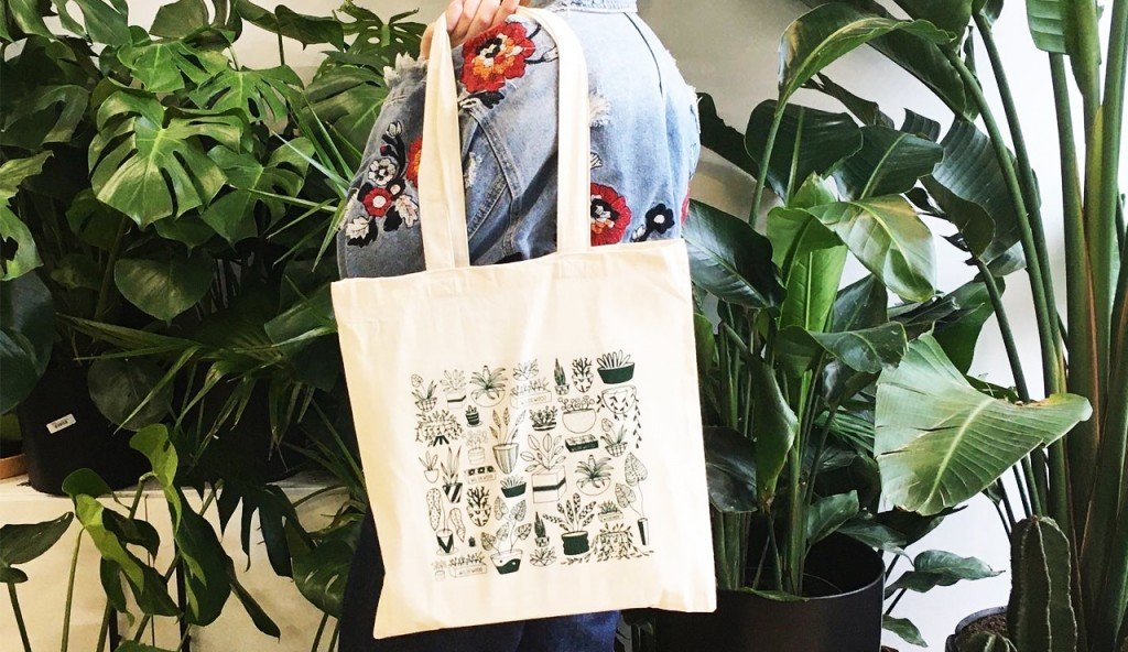 A plant design tote bag slug over a woman's shoulder and the woman is wearing an embroidered jean jacket and is standing in front of a lot of big potted plants