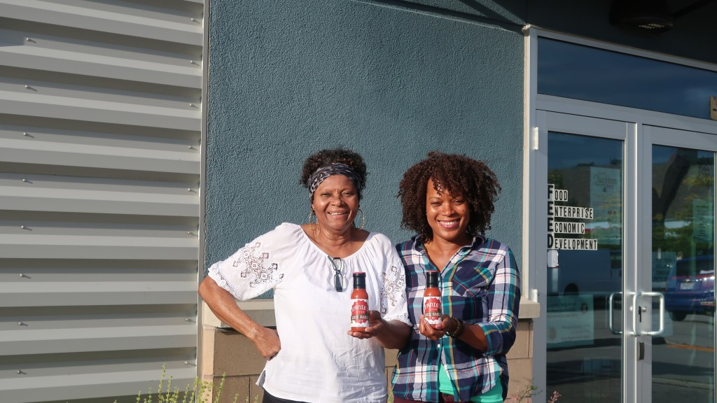 Ernestine Morris and Sandra Morris holding up bottles of their sauce