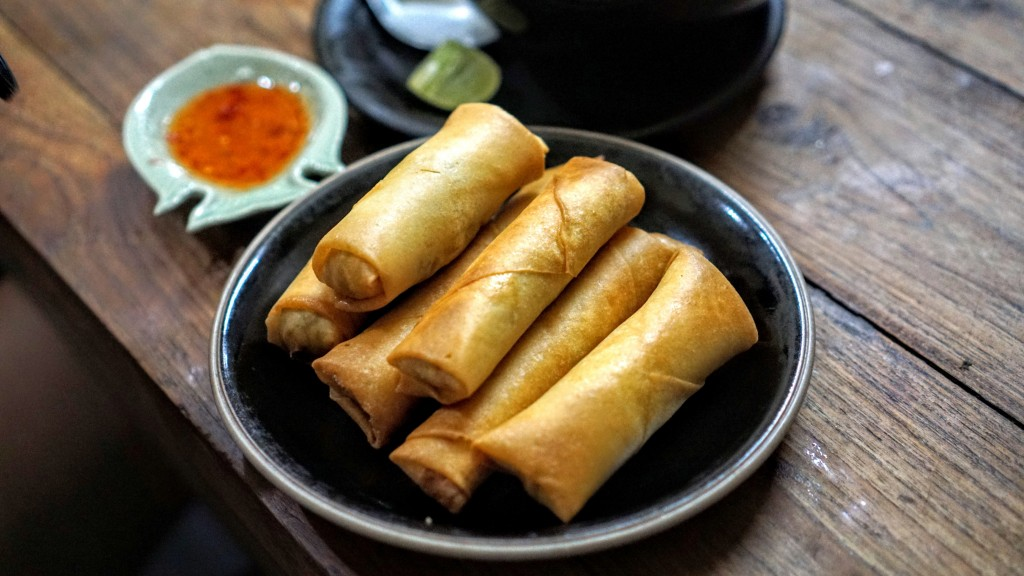 plate of lumpia on a table with some sauces