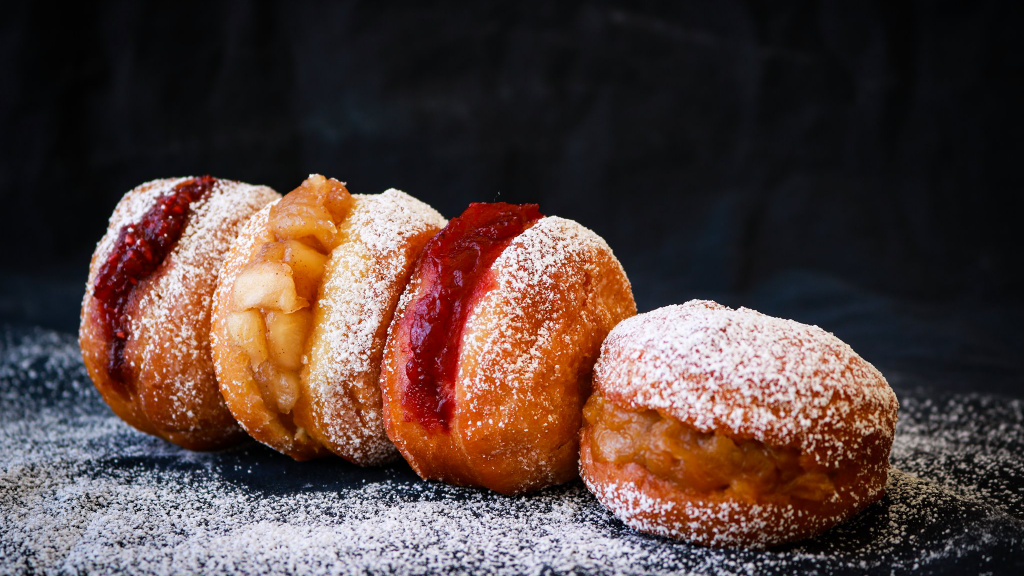 Four custard-filled donuts with powdered sugar on a table.