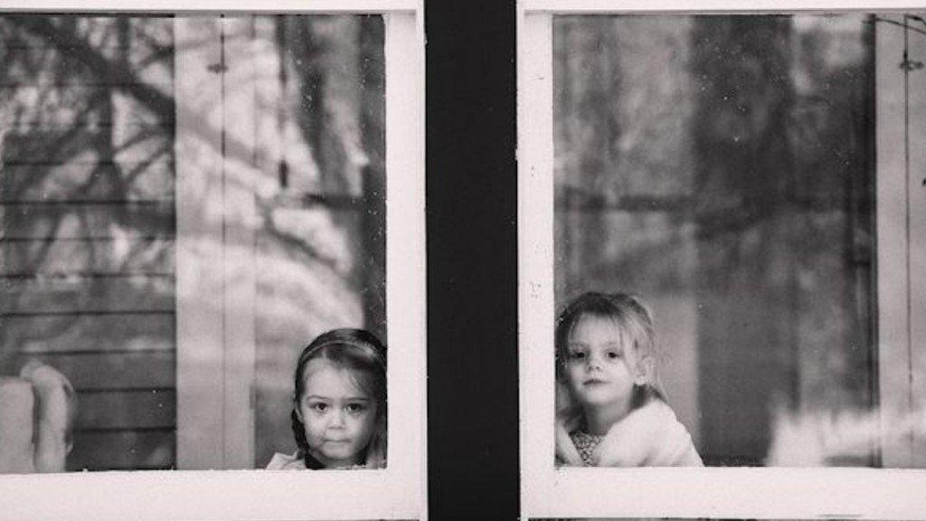 Two girls looking out windows