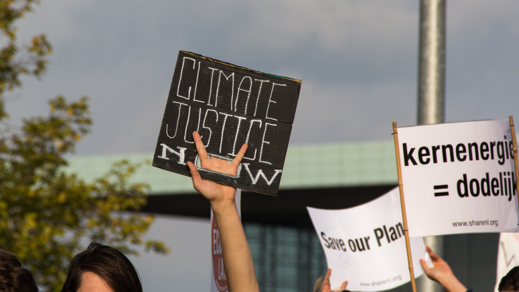 People hold signs to protest climate injustice.
