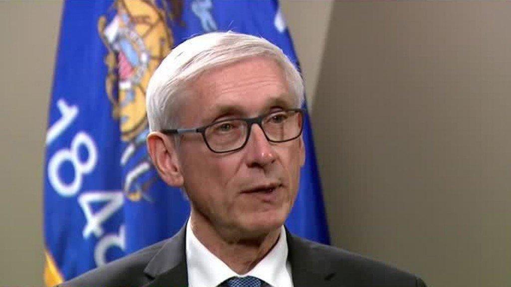 Tony Evers in front of a flag