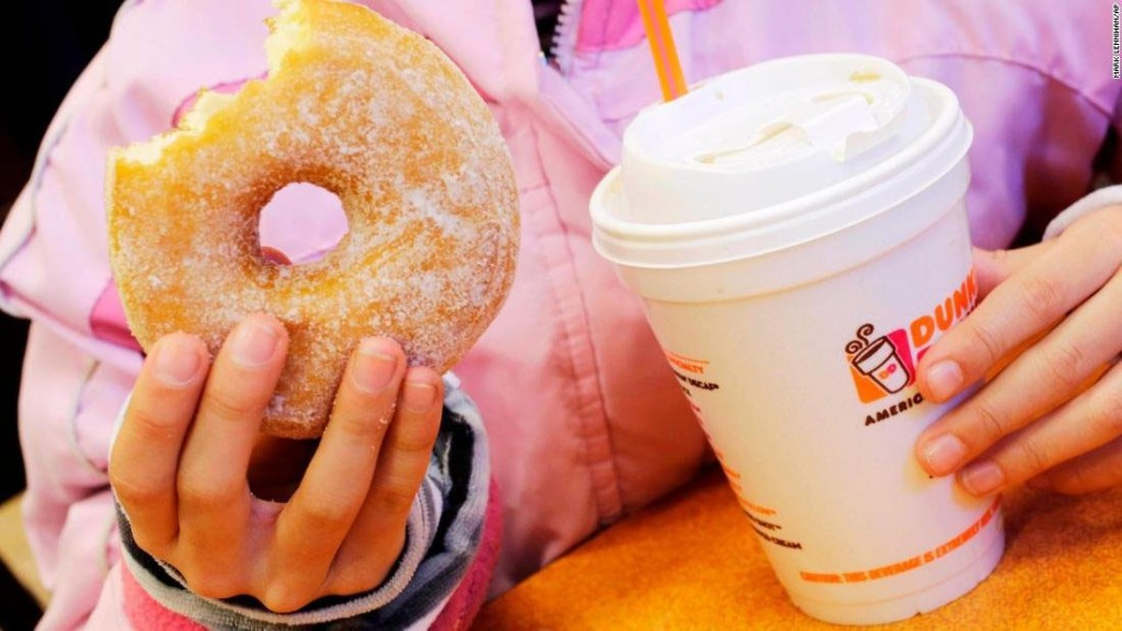 A customer with a beverage served in a foam cup and a doughnut at a Dunkin' Donuts in New York.