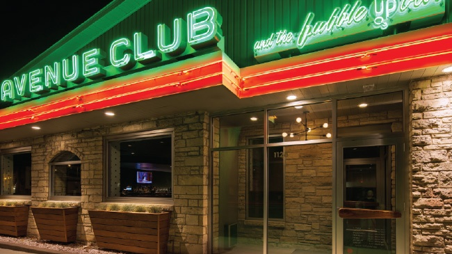 avenue club exterior shot with green neon writing above red neon stripe and stone exterior