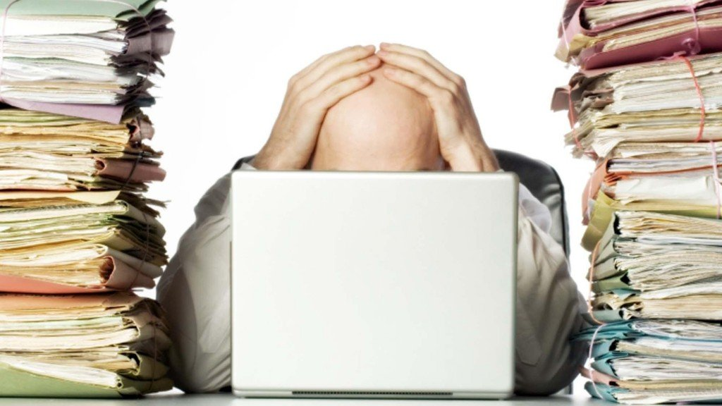 A man clutches his head behind a computer