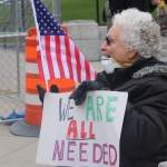 Woman in a lawn chair outside the Capitol wearing a face mask holding an American flag and a sign that says,