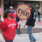A woman in a red Wisconsin pullover holding an American flag and anti-Evers sign