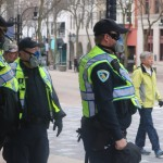 Madison police officers stand on State Street wearing protective masks