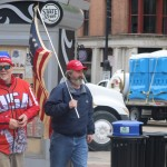 A man carrying an American flag next to a man wearing a USA shirt and Trump hat