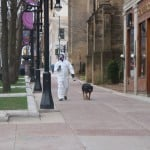 Person wearing a hazmat-type suit and mask is carrying a coffee cup and walking a dog on a leash