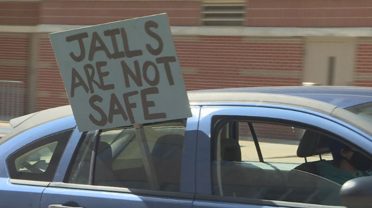 """car with sign, reads """"jails are not safe"""""""