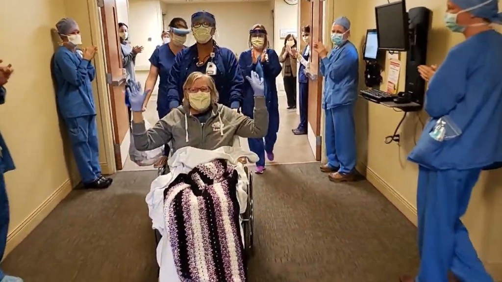 Karen Mcintyre, coronavirus patient, getting applause from staff as she's wheeled out of the hospital