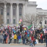 A wide shot outside the capitol shows people many people gathered