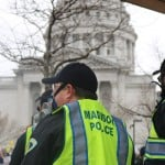 Three Madison officers are seen wearing face masks with the Capitol in the background