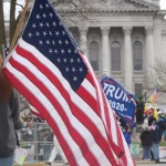 An American flag and part of a Trump 2020 flag are held by people gathered outside the Capitol