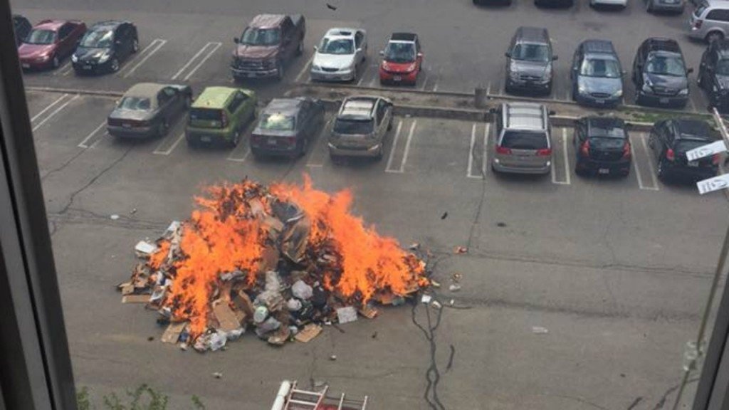 Crews fight large trash fire dumped out of garbage truck into parking lot