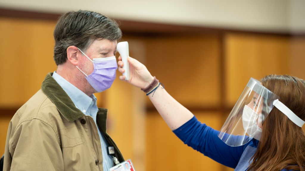 nurse checking temperature of a man in a mask