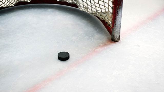 A generic photo of a hockey puck on ice
