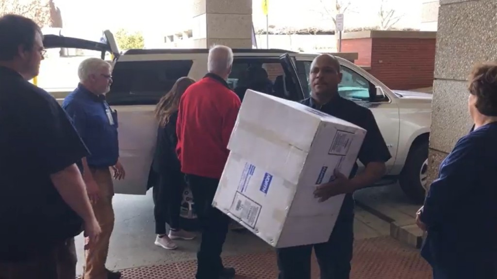 Boxes of donated masks are carried from SUV