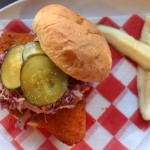 Meatless chicken sandwich on a plate with pickles.