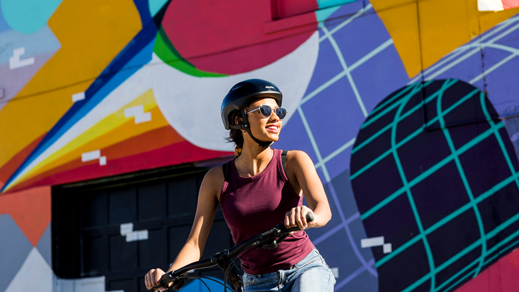A woman in a helmet stopped on a bike holding its handle bars in front of a colorful mural