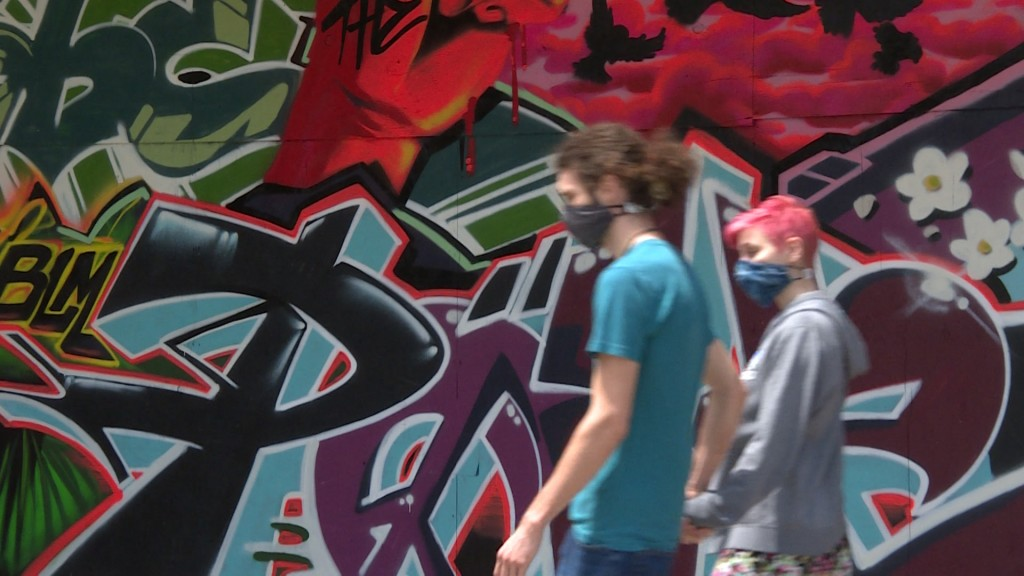 people walk by mural in downtown Madison while wearing masks to protect from the coronavirus