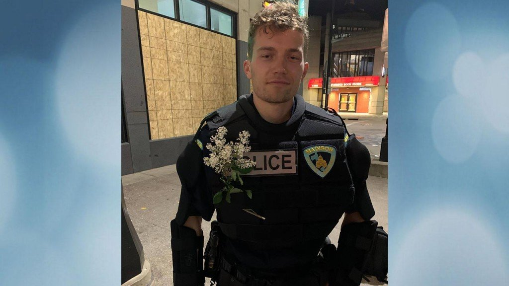 Police Officer With Flowers In Jacket