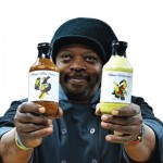 Thony Clarke holding two bottles of his sauce
