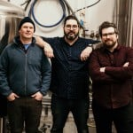 the three owners standing in front of beer barrels