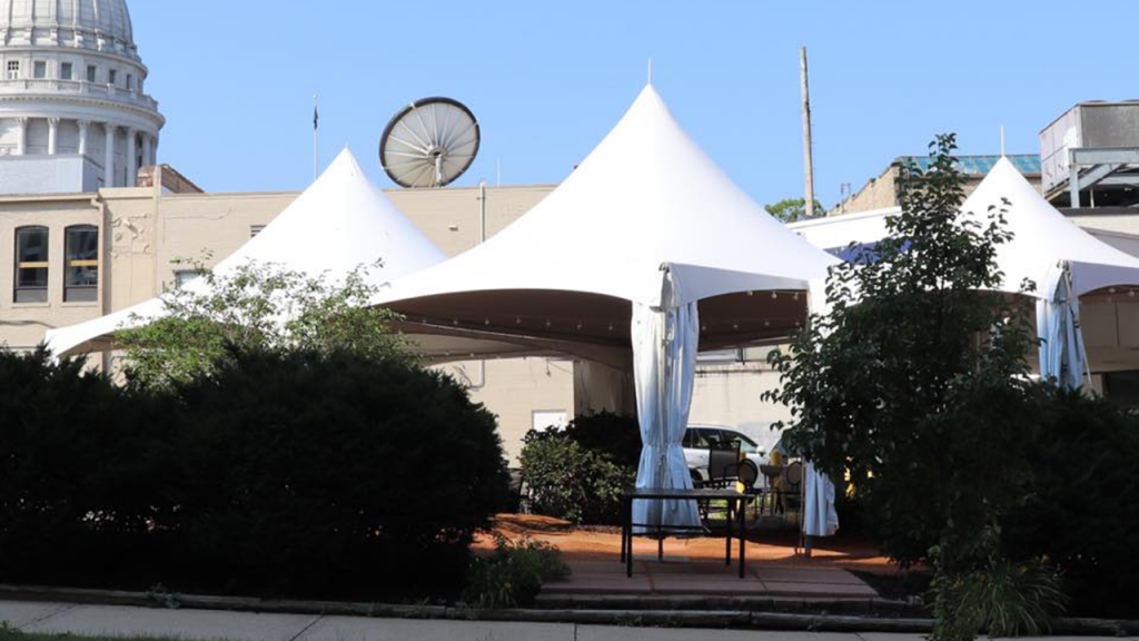 White tent patio at Heritage Tavern with view of the capital building.