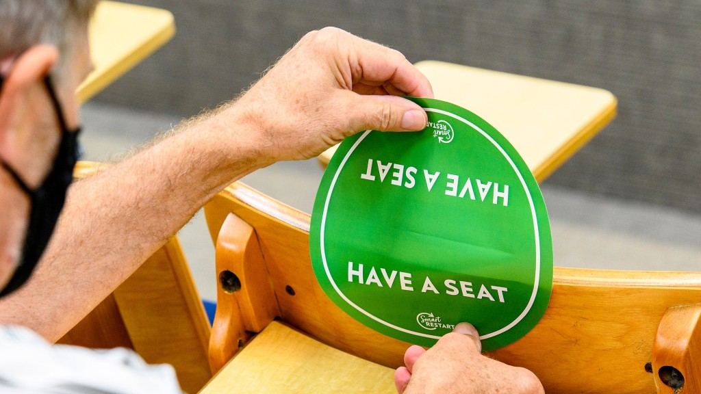 UW staff places seating stickers on chairs.